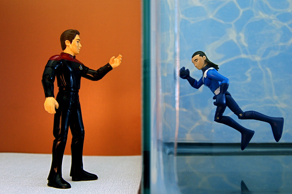 One action figure stands outside of a tank of water looking at another action figure inside of the tank.