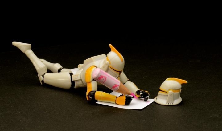 action figure laying down, writing a poem