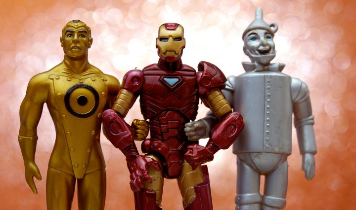 Three action figures standing together with linked arms