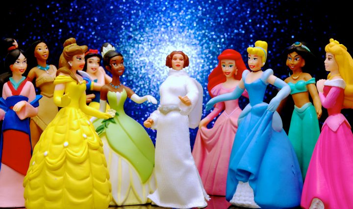 A group of Disney princess action figures standing in a circle and talking to each other.