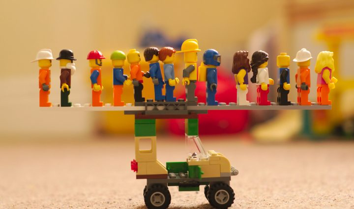 Lego people standing in a line on top of a lego car.