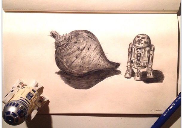 An R2D2 action figure stands on the edge of a page where there is a pencil drawing of a turnip and an R2D2. There is a blue pencil on the right corner of the page.
