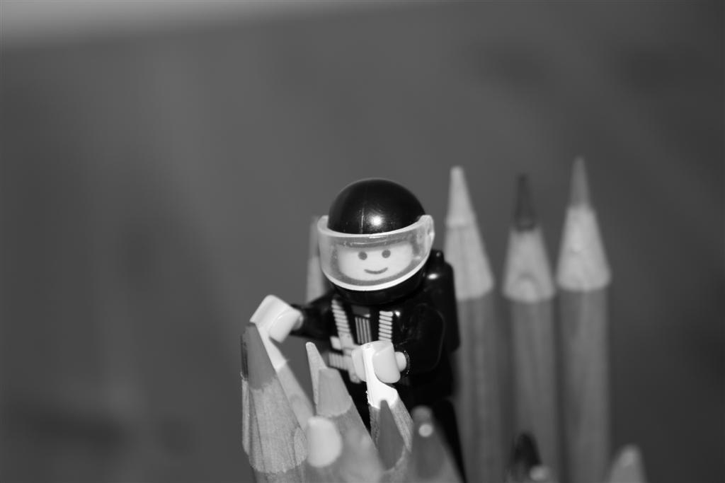A lego character holding on to the edge of two pencils.