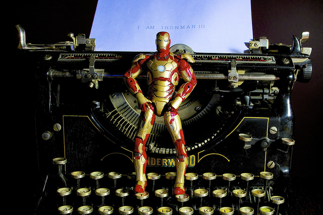 "An iron man action figure stands on a golden typewriter keyboad. In the background, there is a piece of paper coming out of the typewriter on which the action figure has apparently written the words ""I Am Ironman."""