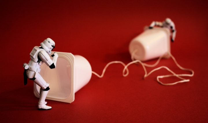 Storm trooper action figures use two white, empty pudding cups connected by a string as a telephone. They're standing on a bright red background.