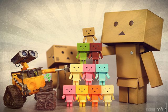 Two figures made out of brown cardboard boxes and the robot from the movie Wall-E stack a pyramid of orange, pink, yellow, green, blue, and red smaller box people.