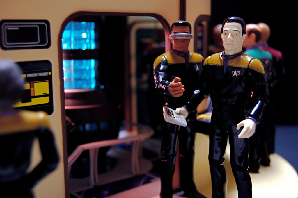 Geordi and Data from Star Trek stand next to each other. Data holds a calculator, and Geordi points to the camera. They're standing in front of a control room.
