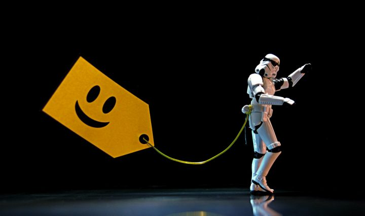 A storm trooper is on the right-hand side of the screen pointing to something that we can't see. There is a yellow tag with a smiley face on the left hand side of the screen with a piece of string that comes off of it that is tied to the storm trooper's waist.