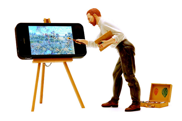 An action figure of the painter Vincent Van Gogh paints water lillies onto the screen of an iPhone that has been set up on an easel. There is a box of paints sitting on the floor behind him.