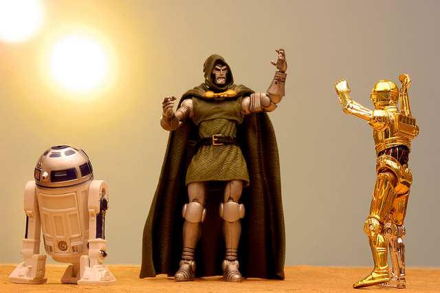 Three action figures from Star Wars stand next to each other. The figure in the middle has his hands raised up like he is talking to the figure on the right. The figure on the right is replying by raising his hands, too.