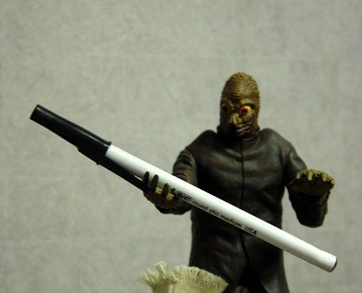 A mole man action figure holding a pen