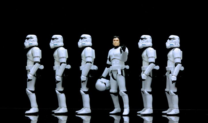 A line of storm troopers stands facing one direction. One in the middle has his mask off and faces the camera.