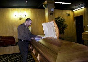 Peter Nieberg stands over a casket TKTKT.