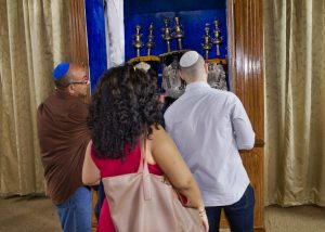 Haim Cheni, left, the congregation's unofficial historian and volunteer caretaker, shows the synagogue's Torahs to visitors. (Photo by Jessica Nieberg)