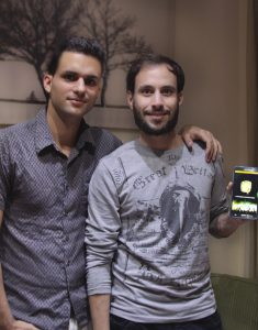 Tech entrepreneurs Juan Louis (r) and Sergio Leon Gonzalez display their phone app, Ke Hay Pa'Hoy, a guide to cultural events in Havana. (Photo by Angelique Couvertier)
