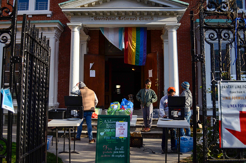 Greenpoint Hunger Program volunteers distribute pre-packed pantry bags on the front lawn of the Greenpoint Reformed Church while taking safety precautions.