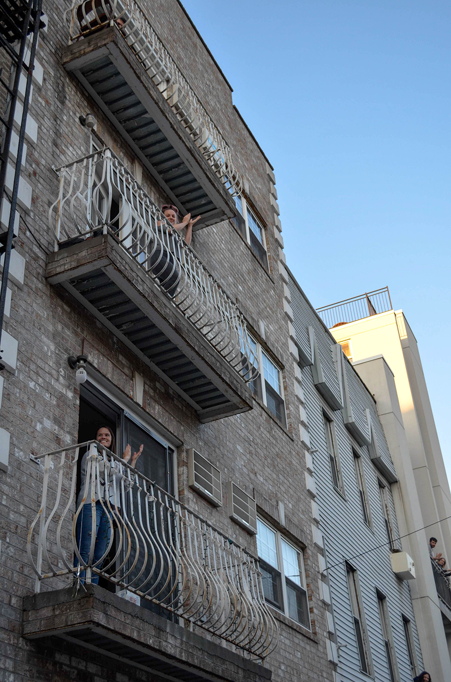 Neighbors are seen applauding essential workers from their balconies on Dupont Street.