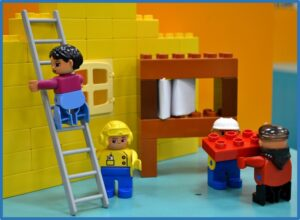 two pens on an angle pointing down toward finished lego building with lego people working together