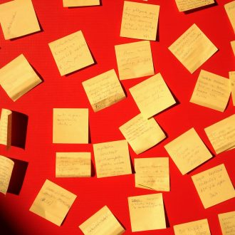 A red wall with yelow post-it notes. The messages on the notes are not legible.