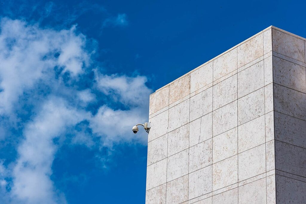 Image of security camera on the side of a nondescript cement building.