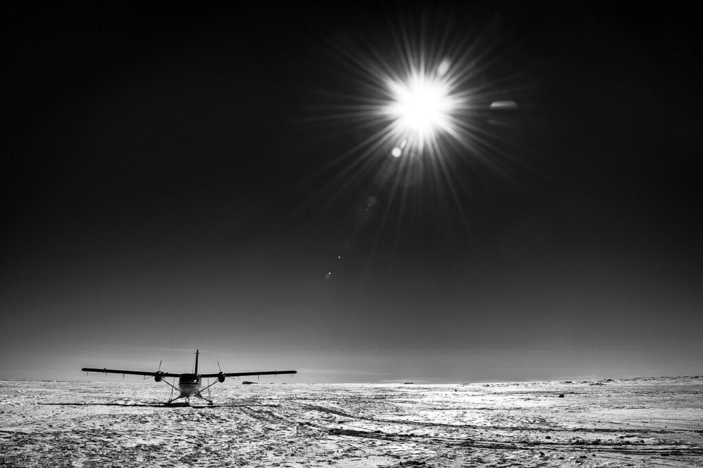 Black and white image of a small plane sitting on ice.