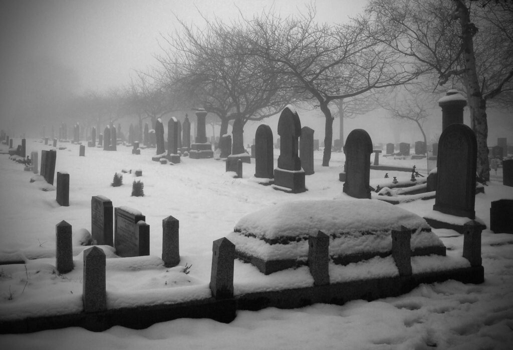 Black and white image of a snowy graveyard.