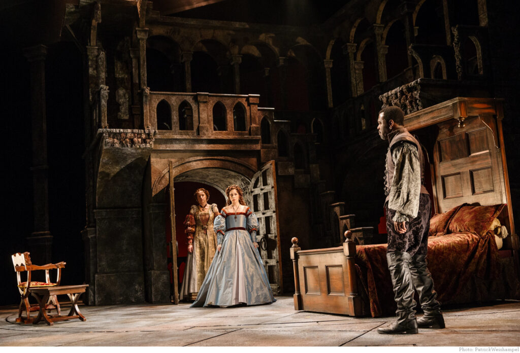Photo of a stage performance of Othello. Image depicts a stage set with wooden bed room furniture. Two women are entering the bedroom and a man, Othello, is standing on the right side of the stage.