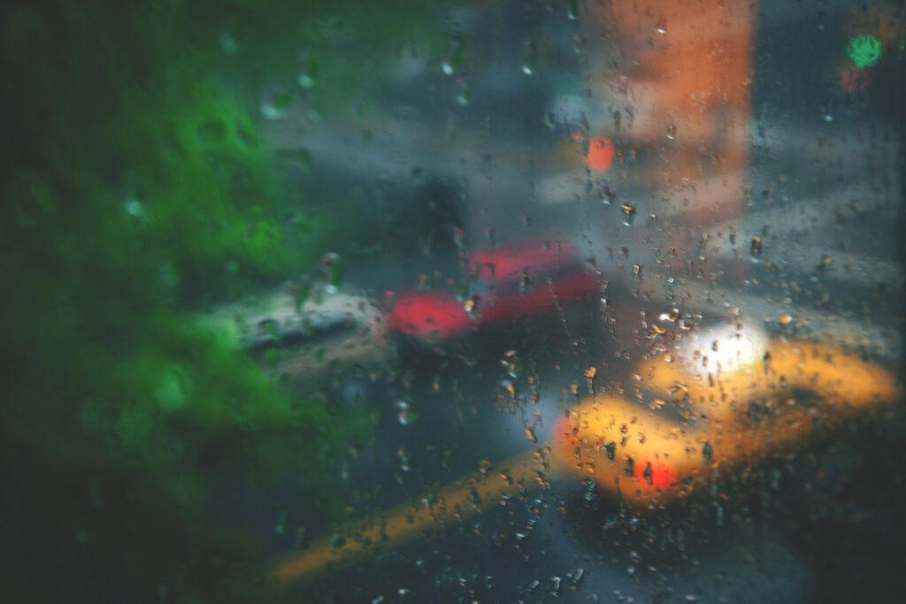 Image of city street through a rain dappled window.