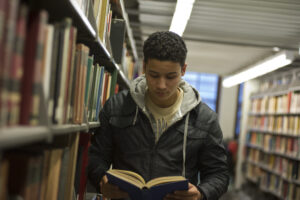 Student reading a book in the stacks