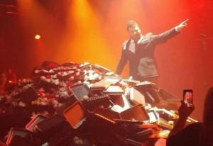 Pantelis Pantelidis onstage, with a mountain of audience-thrown flowers. Taken from www.mixanitouxronou.gr/