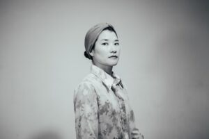 black and white photo of kate-hers RHEE in turban and collared jacket